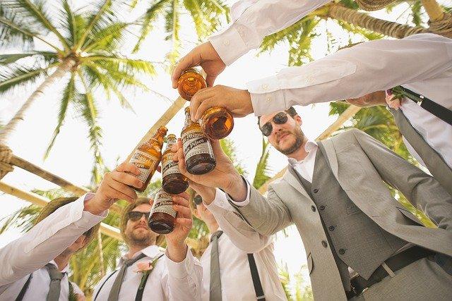 muži si připíjejí pivem